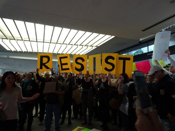 resist-sign-with-large-crowd-at-sfo-1-29-17-small